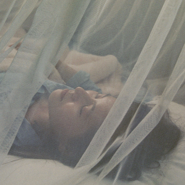 Sleeping under a mosquito net (Photo by Chris Clogg)